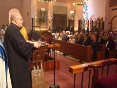 Rev. Fr. Mardiros Shevian благодари от трибуната на кмета на Ню Йорк Майкъл Блумберг и на бизнесмена Сетрак Агонян, чиято корпорация създаде новата бронзова входна врата на Катедралата /първите двама в дясно на пейката/.