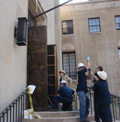 Работници, в присъствието на г-н Агонян, инсталират  бронзовата врата на Катедралата.